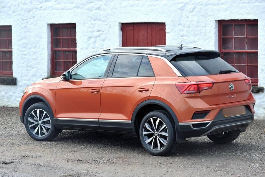 orange suv parked beside white concrete building 3610342